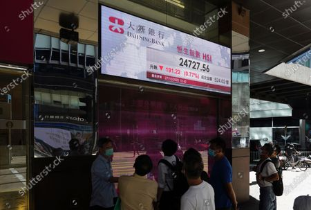 People walk past a bank's electronic board showing the Hong Kong share index at Hong Kong Stock Exchange . Shares skidded in Asia on Tuesday after surging coronavirus cases and waning hopes for U.S. economic stimulus gave Wall Street its worst day in a month
