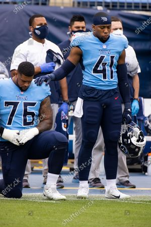 Tennessee Titans running back Khari Blasingame (41) stands for the national anthem and puts his hand on the kneeling shoulder of offensive guard Rodger Saffold (76) before an NFL football game against the Pittsburgh Steelers, in Nashville, Tenn