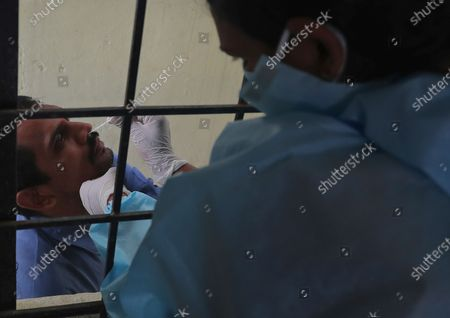 Health worker takes a nasal swab sample at a COVID-19 testing center in Hyderabad, India, . India reports 36,470 new coronavirus cases, the lowest in more than three months in a continuing downward trend. However, the overall tally neared 8 million, the second in the world behind the U.S. with over 8.7 million positive cases