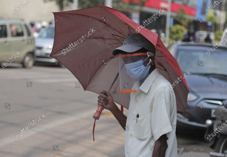 Foto de Man wearing a face shield as a precautionary measure against the coronavirus walks on a street in Hyderabad, India, . India reports 36,470 new coronavirus cases, the lowest in more than three months in a continuing downward trend. However, the overall tally neared 8 million, the second in the world behind the U.S. with over 8.7 million positive cases