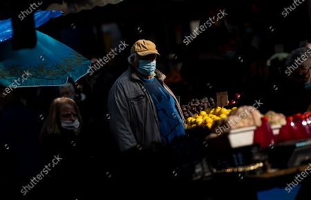 Stock Picture of A man wearing a face mask buys vegetables at a large open market in Sofia, Bulgaria, 27 October 2020. Bulgaria continues to record almost every day a new record of COVID-19 positives over the last three weeks. The number of deaths in 24 hours reached 42. Prime Minister Boyko Borisov tested positive on 25 October and works in quarantine at home, as do seven of the 17 ministers who have been in contact with Borisov in the last few days.