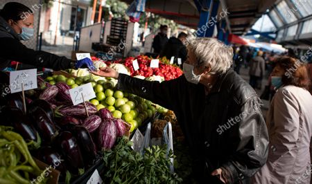 A woman wearing a face mask buys vegetables at a large open market in Sofia, Bulgaria, 27 October 2020. Bulgaria continues to record almost every day a new record of COVID-19 positives over the last three weeks. The number of deaths in 24 hours reached 42. Prime Minister Boyko Borisov tested positive on 25 October and works in quarantine at home, as do seven of the 17 ministers who have been in contact with Borisov in the last few days.