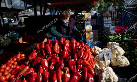 Stock Image of A seller wearing a face mask arranges goods at a large open market in Sofia, Bulgaria, 27 October 2020. Bulgaria continues to record almost every day a new record of COVID-19 positives over the last three weeks. The number of deaths in 24 hours reached 42. Prime Minister Boyko Borisov tested positive on 25 October and works in quarantine at home, as do seven of the 17 ministers who have been in contact with Borisov in the last few days.