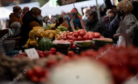 A seller wearing a face mask shows an eggplant to a customer at a large open market in Sofia, Bulgaria, 27 October 2020. Bulgaria continues to record almost every day a new record of COVID-19 positives over the last three weeks. The number of deaths in 24 hours reached 42. Prime Minister Boyko Borisov tested positive on 25 October and works in quarantine at home, as do seven of the 17 ministers who have been in contact with Borisov in the last few days.