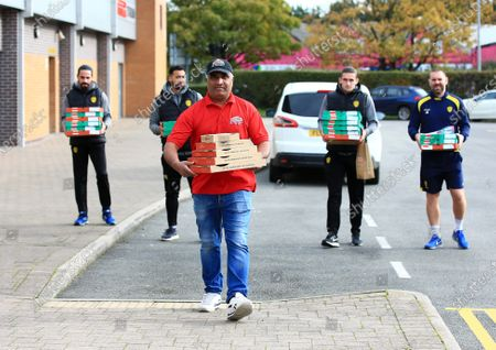 Stock Picture of A Papa John's delivery driver arrives at the Pirelli Stadium holding pizza boxes along with Burton Albion manager Jake Buxton and players Ben Fox, Kane Hemmings and Ryan Edwards