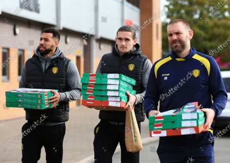 Burton Albion manager Jake Buxton and players Ben Fox and Kane Hemmings arrive at the Pirelli stadium with free Papa John's pizza