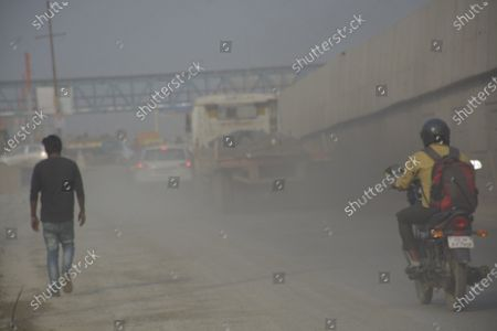Commuters travel on a dust covered road amid rising air pollution, on October 26, 2020 in Ghaziabad, India.