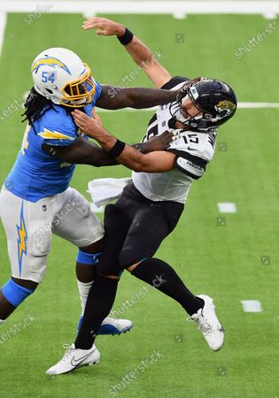 Jacksonville Jaguars quarterback Gardner Minshew II (15) gets hit by Los Angeles Chargers defensive end Melvin Ingram (54) while throwing a pass, in Inglewood, Calif. The Chargers defeated the Jaguars 39-29