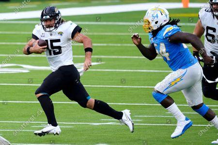 Jacksonville Jaguars quarterback Gardner Minshew, left, scrambles away from Los Angeles Chargers defensive end Melvin Ingram during the second half of an NFL football game, in Inglewood, Calif