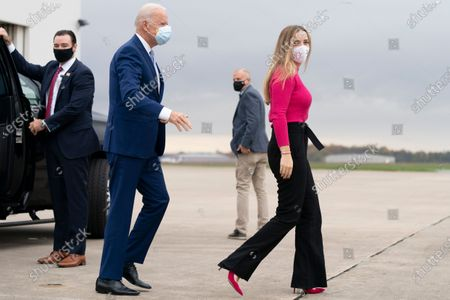 Democratic presidential candidate former Vice President Joe Biden and his granddaughter Finnegan Biden, right, arrive to board his campaign plane at New Castle Airport in New Castle, to travel to Georgia for rallies