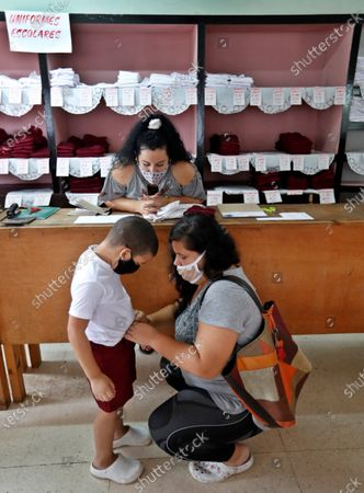 Stock Image of A mother tries on her son a school uniform for sale, in Havana, Cuba, 27 October 2020. The Cuban capital is preparing to begin the school year, interrupted by the pandemic, on November 2 and with sanitary measures according to the new normal, such as the use of a mask, hand washing and social distancing.