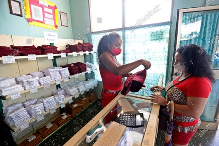 A woman (R) buys the school uniform for her son, in Havana, Cuba, 27 October 2020. The Cuban capital is preparing to begin the school year, interrupted by the pandemic, on November 2 and with sanitary measures according to the new normal, such as the use of a mask, hand washing and social distancing.