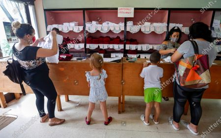 Two mothers buy the school uniform for their son, in Havana, Cuba, 27 October 2020. The Cuban capital is preparing to begin the school year, interrupted by the pandemic, on November 2 and with sanitary measures according to the new normal, such as the use of a mask, hand washing and social distancing.