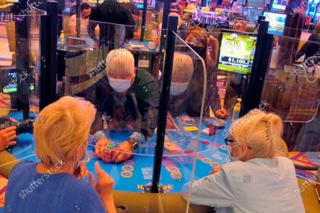 See-through barriers separate gamblers and a dealer at a card table at the Hard Rock casino in Atlantic City, N.J., on July 2, 2020, the first day it reopened after being closed for four months due to the coronavirus outbreak. American Gaming Association President Bill Miller said, the industry is adapting to the pandemic but needs assistance from the government for its casinos and workers