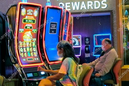 Gamblers wear face masks while playing slot machines at the Hard Rock casino in Atlantic City, N.J., on July 2, 2020, the first day it reopened after being closed for four months due to the coronavirus outbreak. American Gaming Association President Bill Miller said, the industry is adapting to the pandemic but needs assistance from the government for its casinos and workers