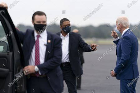 Democratic presidential candidate former Vice President Joe Biden speaks with Rep. Cedric Richmond, D-La., center, as he arrives at Columbus Airport in Columbus, Ga., to travel to Warm Springs, Ga. for a rally