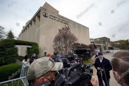 Pittsburgh Mayor Bill Peduto, second from right, is interviewed outside the Tree of Life synagogue in Pittsburgh after attending a moment of silence, the second anniversary of the shooting at the synagogue that killed 11 worshippers