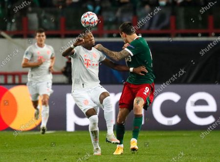 Bayern's David Alaba, left, and Lokomotiv's Fyodor Smolov challenge for the ball during the Champions League group A soccer match between Lokomotiv Moscow and Bayern Munich in Moscow, Russia