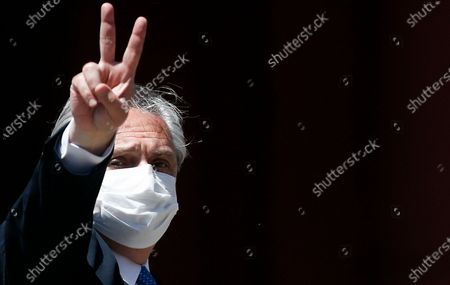 President Alberto Fernandez, wearing a mask amid the COVID-19 pandemic, flashes a victory sign as he arrives at the government house for a ceremony honoring late President Nestor Kirchner on the 10-year anniversary of his death in Buenos Aires, Argentina, . Kirchner's widow, Cristina Fernandez, is the current vice president