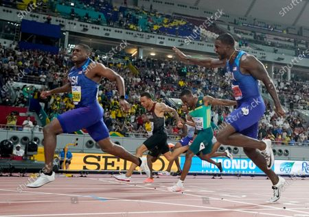 Christian Coleman, of the United States, crosses the finish line to win the men's 100 meter final ahead of silver medalist Justin Gatlin, right, also of the United States, during the World Athletics Championships in Doha, Qatar. Men's 100-meter world champion Christian Coleman was banned for two years, because of three violations of doping control rules