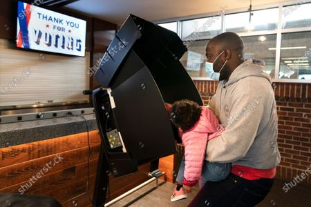 """Stock Image of Ron Williams, Jr., of Washington, has his daughter Mimi Williams, 2, help him to push the button while casting his vote at an early voting center at Nationals Park, in Washington. """"We anticipated lines on election day,"""" says Williams, """"and I want to get this over with as November 4th can't come soon enough. I brought my daughter so that when she is older she will see that voting is powerful and a way to get our voices heard"""