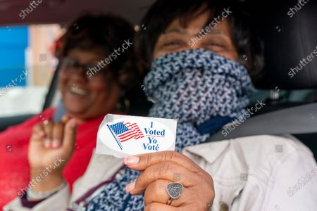 """Patria, 57, right, who asked to use only her first name, and Janet Wilson, 68, both of Washington, smile after receiving their """"I Voted"""" stickers in a car after submitting their ballots from the curbside voting line, at Malcolm X Opportunity Center, an early voting center in Washington. Curbside voting is offered at this location for seniors and people with disabilities. """"I voted early because I want to be sure that my health doesn't keep me from voting on the 3rd,"""" says Wilson, """"the primary voting was so crowded that I couldn't vote, so this time I'm voting early"""