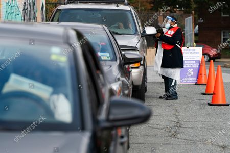 Poll worker Sheila Thomas helps voters to submit their ballots from the curbside voting line, at Malcolm X Opportunity Center, an early voting center in Washington. Curbside voting is offered at this location for seniors and people with disabilities