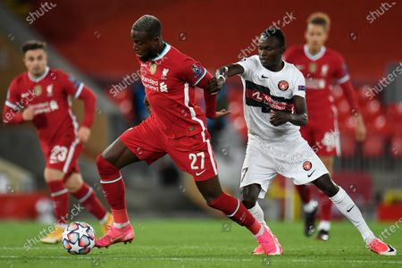 Liverpool's Divock Origi and Midtjylland's Pione Sisto, right, vie for the ball during the Champions League Group D soccer match between Liverpool and FC Midtjylland at Anfield stadium, in Liverpool, England