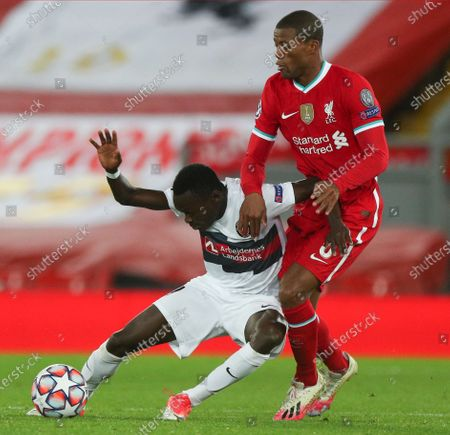 Midtjylland's Pione Sisto, left, and Liverpool's Georginio Wijnaldum vie for the ball during the Champions League Group D soccer match between Liverpool and FC Midtjylland at Anfield stadium, in Liverpool, England