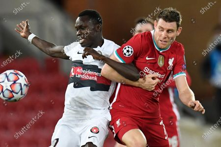 Liverpool's James Milner, right, and Midtjylland's Pione Sisto lock arms during the Champions League Group D soccer match between Liverpool and FC Midtjylland at Anfield stadium, in Liverpool, England