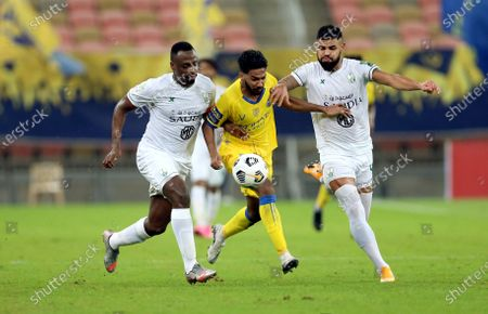 Al-Ahli's players Lucas Lima (R) and Motaz Hawsawi (L) in action against Al-Nassr's Khalid Al-Ghannam (C) during the Semi-finals of the King's Cup match between Al-Ahli and Al-Nassr at King Abdullah Sport City Stadium, 30 kilometers north of Jeddah, Saudi Arabia, 27 October 2020.