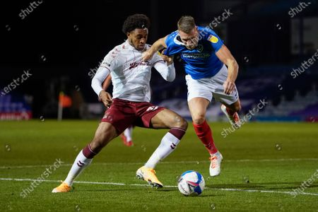Stock Image of Caleb Chukwuemeka of Northampton Town and Lee Brown of Portsmouth battle for the ball during the EFL Sky Bet League 1 match between Portsmouth and Northampton Town at Fratton Park, Portsmouth