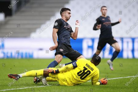 Manchester City's Ferran Torres (L) scores the 1-0 lead against Olympique Marseille's goalkeeper Steve Mandanda (down) during the UEFA Champions League Group C soccer match between Marseille and Manchester City at the Orange Velodrome stadium, in Marseille, France 27 October 2020.