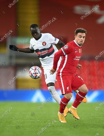 Midtjylland's Awer Mabil, left, competes for the ball with Liverpool's Xherdan Shaqiri during the Champions League Group D soccer match between Liverpool and FC Midtjylland at Anfield stadium, in Liverpool, England