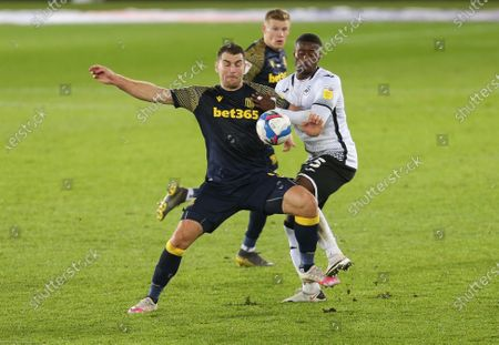 Stock Photo of Sam Vokes of Stoke City and Marc Guehi of Swansea City compete for the ball