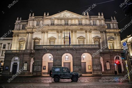 """Stock Photo of Military vehicle drives past La Scala opera theater in Milan, northern Italy. The number of performers at Milan's famed La Scala opera house positive with the coronavirus has risen to 21, even as the theater was forced to close due to new government restrictions aimed at curbing the virus' resurgence. La Scala spokesman Paolo Besana confirmed Tuesday that 18 members of the world-class chorus and three woodwind players in the orchestra have the virus. That comes after two singers, including tenor Francesco Meli, tested positive, ahead of planned concert performances last week of """"Aida"""