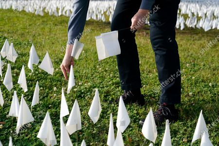 "Volunteer adds white flags to a temporary art installation in remembrance of Americans who have died of COVID-19, near Robert F. Kennedy Memorial Stadium in Washington. Artist Suzanne Brennan Firstenberg's installation, called ""In America, How Could This Happen,"" will include an estimated 240,000 flags when completed"