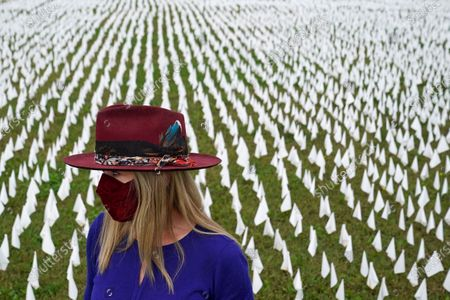 "Artist Suzanne Brennan Firstenberg stands among thousands of white flags planted in remembrance of Americans who have died of COVID-19, near Robert F. Kennedy Memorial Stadium in Washington. Firstenberg's temporary art installation, called ""In America, How Could This Happen,"" will include an estimated 240,000 flags when completed"
