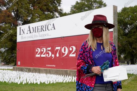 "Stock Photo of Artist Suzanne Brennan Firstenberg stands near her art installation of white flags planted in remembrance of Americans who have died of COVID-19, near Robert F. Kennedy Memorial Stadium in Washington. The temporary installation, called ""In America, How Could This Happen,"" will include an estimated 240,000 flags when completed"