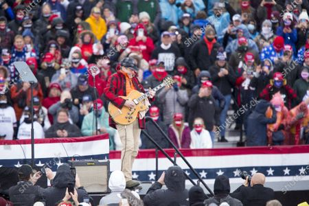 Stock Photo of Ted Nugent plays guitar while waiting for US President Donald J. Trump to arrive during a campaign visit to Capital Region International Airport, Lansing, Michigan, USA, 27 October 2020.