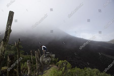 National park ranger Guillermo Carrera climbs over a fence to get to the Pacaya Volcano in Escuintla, Guatemala, . Authorities are evaluating the possibility of reopening the Volcan de Pacaya National Park after being closed for several months as a measure to curb the spread of COVID-19