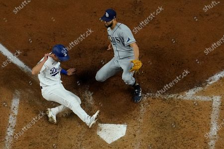 Los Angeles Dodgers' Austin Barnes scores past Tampa Bay Rays relief pitcher Nick Anderson ons a wild pitch during the sixth inning in Game 6 of the baseball World Series, in Arlington, Texas