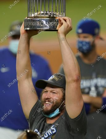 Los Angeles Dodgers pitcher Clayton Kershaw celebrates with the trophy after defeating the Tampa Bay Rays 3-1 to win the baseball World Series in Game 6, in Arlington, Texas