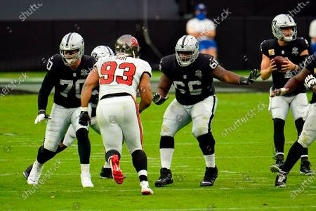 Las Vegas Raiders offensive tackle Sam Young (70) and Las Vegas Raiders offensive guard Gabe Jackson (66) attempt to block Tampa Bay Buccaneers defensive end Ndamukong Suh (93) during the first half of an NFL football game, in Las Vegas