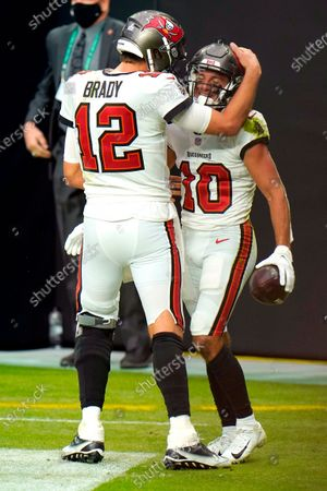 Tampa Bay Buccaneers quarterback Tom Brady (12) celebrates with after throwing a touchdown to wide receiver Scott Miller (10) against the Las Vegas Raiders during the first half of an NFL football game, in Las Vegas