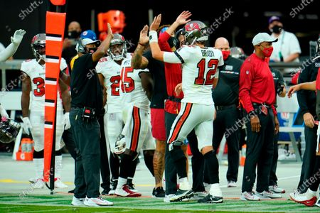 Tampa Bay Buccaneers quarterback Tom Brady (12) celebrates with his teammates on the sideline after throwing a touchdown to wide receiver Scott Miller (10) against the Las Vegas Raiders during the first half of an NFL football game, in Las Vegas