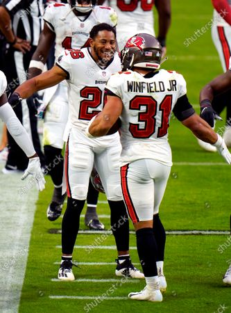 Tampa Bay Buccaneers defensive back Andrew Adams (26) reacts after teammate Tampa Bay Buccaneers strong safety Antoine Winfield Jr. (31) forced an interception turnover against the Las Vegas Raiders during the second half of an NFL football game, in Las Vegas