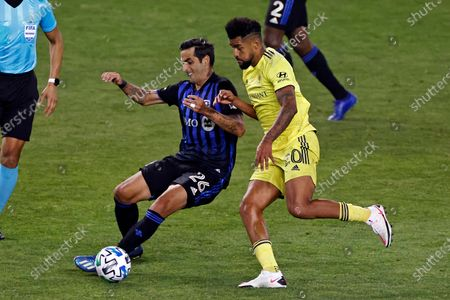Montreal Impact defender Jorge Luis Corrales (26) controls the ball in front of Nashville SC midfielder Anibal Godoy (20) during the first half of an MLS soccer match, in Harrison, N.J