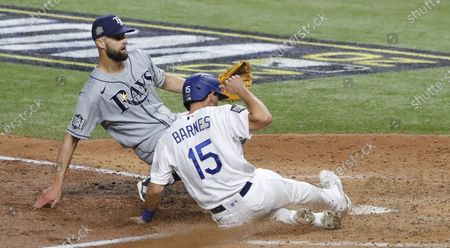 Los Angeles Dodgers baserunner Austin Barnes scores in front of Tampa Bay Rays pitcher Nick Anderson (L) on a wild pitch in the bottom of the sixth inning of Major League Baseball's World Series Game six at Globe Life Field in Arlington, Texas, USA, 27 October 2020. The Dodgers lead the best-of-seven series 3-2.