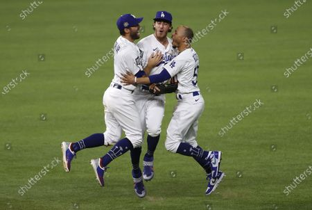 Stock Photo of Los Angeles Dodgers players (L-R) Chris Taylor, Cody Bellinger and Mookie Betts celebrate after defeating the Tampa Bay Rays in Major League Baseball's World Series Game six to win the World Series at Globe Life Field in Arlington, Texas, USA, 27 October 2020. The Dodgers win the best-of-seven series 4-2.